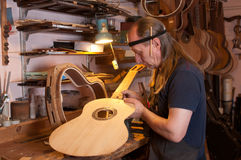 Luthier. Russian luthier in his studio. Manufacture acoustic guitars. Equipment for the production of guitars and balalaika. Manufacture, repair and restoration Royalty Free Stock Image