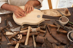 The luthier builds a medieval stringed instrument. Luthier working on the creation of a stringed instrument. Various tools and instrument are placed on the Royalty Free Stock Photo