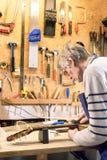 Luthier classant les frettes d'une guitare acoustique images libres de droits