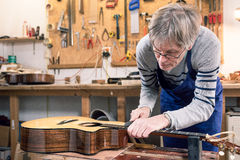 Luthier classant les frettes d'une guitare acoustique photos libres de droits