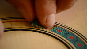 Luthier decorates handmade guitar, extreme close up Stock Photos