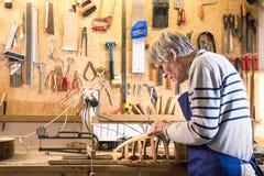Luthier die bij zijn luit aan de werkbank werken Stock Afbeelding