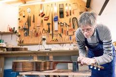Luthier die de lijstwerken van een akoestische gitaar indienen stock afbeeldingen
