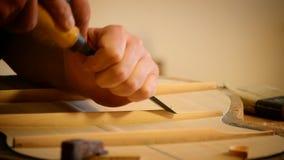 Luthier die een gitaarstructuur met een beitel maken stock videobeelden