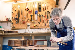 Luthier filing the frets of an acoustic guitar Stock Images