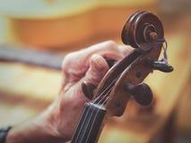 Luthier Hände des alten Mannes, die gealterte Violine abstimmen Stockbild