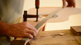 Luthier mäter en gitarr med en regel lager videofilmer