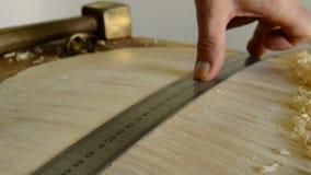 Luthier mäter en gitarr med en regel arkivfilmer