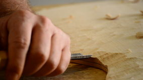 Luthier manufacturing a guitar with chisel in workplace, close up stock footage