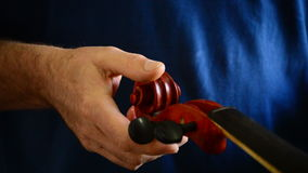 Luthier placing the pins in a violin or viola in the workplace stock footage
