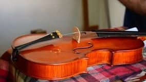 Luthier que trabaja con un instrumento del violín en lugar de trabajo almacen de video