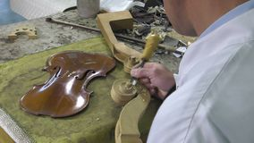 Luthier sculpt a cello head stock footage