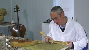 Luthier sculpt a cello head stock video footage