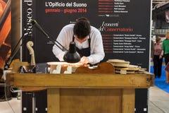 Luthier som arbetar på en fiol på biten 2014, internationellt turismutbyte i Milan, Italien arkivbild