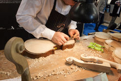 Luthier som arbetar på en fiol på biten 2014, internationellt turismutbyte i Milan, Italien royaltyfri bild