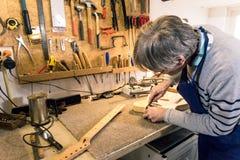 Luthier som sparar neckpocketen av en elektrisk gitarr Royaltyfria Bilder