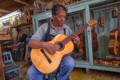 Luthier w Paracho Meksyk bada gitarę w jego sklepie Fotografia Royalty Free