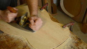 Luthier working in a flamenco guitar with a wood planer stock video footage
