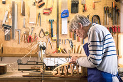 Luthier working at his lute on the workbench Stock Image