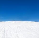 Lutning för vinterbergsnö och blå himmel Arkivbilder