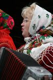 Woman plays the accordion. LUTSK, UKRAINE - 10 January 2009: Woman with glasses and kerchief plays the accordion on the street Stock Image