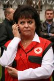 Woman talks on the phone. LUTSK , UKRAINE - 12 September 2008: Woman in clothes with logo of the Red Cross talks on the phone at camp for refugees Stock Photos