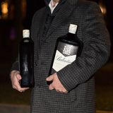 Man with bottles of whiskey. Lutsk, Volyn / Ukraine - November 17 2017: Man with two big bottles of scotch whiskey posing at park Stock Image