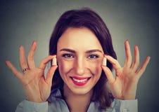 Lutte contre le bruit Femme tenant des prises d'oreille photos stock