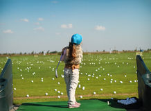 Luttle girl swinging golf club. Little girl swinging golf club, rear view Royalty Free Stock Images
