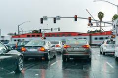 Luty 2, 2019 Sunnyvale, CA, usa/- pojazdy czeka przy czerwonym światła ruchu; wysoki prędkość pociąg przechodzi w tle, San fotografia stock
