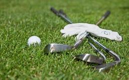 Luva, bola e clubes de golfe no campo de golfe Imagem de Stock Royalty Free