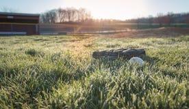 A luva de beisebol e o basebol no campo de basebol no amanhecer orvalham Imagens de Stock Royalty Free