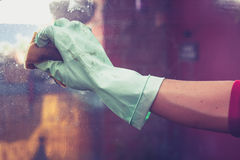 A luva de borracha vestindo da mão está limpando janelas Imagens de Stock