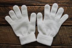 Luvas brancas do inverno das meninas isoladas no fundo de madeira Imagens de Stock Royalty Free