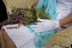 Luvas brancas e flores roxas fotos de stock