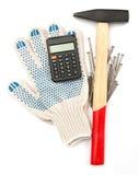 Luvas com martelo e calculadora Fotografia de Stock Royalty Free