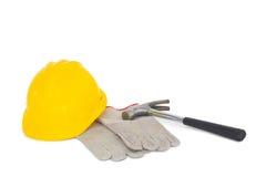 Luvas com martelo e capacete de segurança no fundo branco Fotografia de Stock