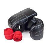 Luvas de encaixotamento pretas e atadura elástica vermelha isolada no fundo branco Fotografia de Stock Royalty Free
