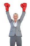 Luvas de encaixotamento vestindo da mulher de negócios feliz e levantamento de seus braços Foto de Stock Royalty Free