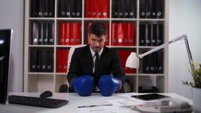 Luvas de encaixotamento vestindo do homem de negócios no escritório video estoque