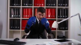 Luvas de encaixotamento vestindo do homem de negócios no escritório vídeos de arquivo