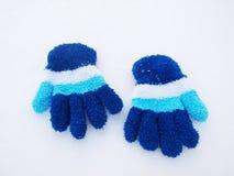 Luvas do inverno das crianças na neve Imagens de Stock