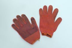 Luvas do trabalho do algodão laranja-vermelho um é interior girado - para fora par Imagens de Stock Royalty Free