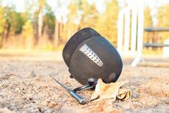 Luvas equestres e chicote do capacete esquecidos na terra Fotografia de Stock