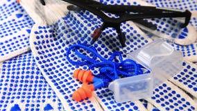 Luvas finas do trabalho com espinhas azuis, vidros protetores e tomadas da orelha em uma superfície de giro, filme