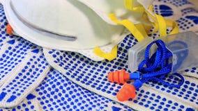 Luvas finas do trabalho com espinhas, os respiradores e as tomadas azuis da orelha em uma superfície de giro, vídeos de arquivo
