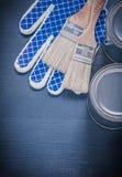 Luvas protetoras das latas das escovas de pintura em de madeira Foto de Stock Royalty Free
