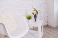 Luxe en minimalistic wit huisbinnenland met stoel, koffietafel met tropische installatie in vaas Exemplaarruimte voor stock foto's
