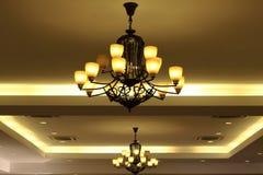 Luxe het gele kroonluchter hangen onder plafond in de ruimte Royalty-vrije Stock Foto's