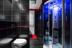 Luxe high-tech bathroom idea. High gloss black bathroom with toilet and shower with hydromassage Royalty Free Stock Photo